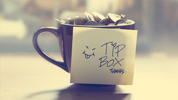 Coffee Mug Filled With Coins With A Post-it Saying Tip Box, Thanks