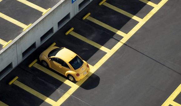 Yellow VW Beetle Parked Between Yellow Lines On Black Asphalt