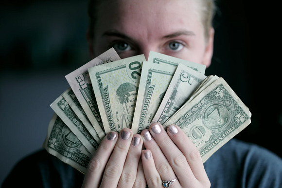 Woman Fanning Money In Front Of Her Face