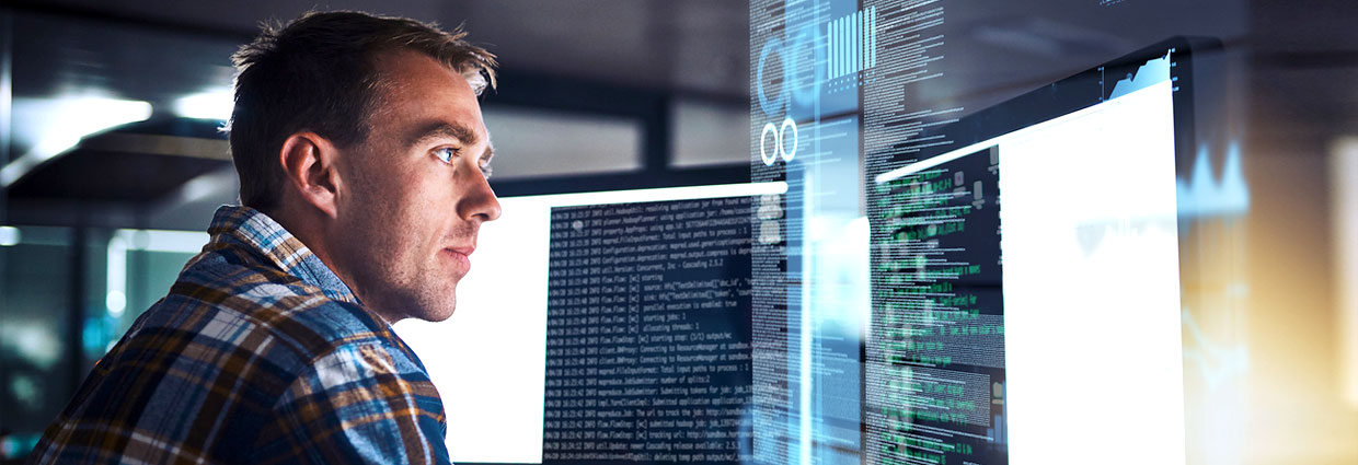 Male IT person reviewing computer system code on multiple monitors