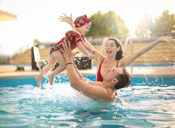 Young Family In Swimming Pool