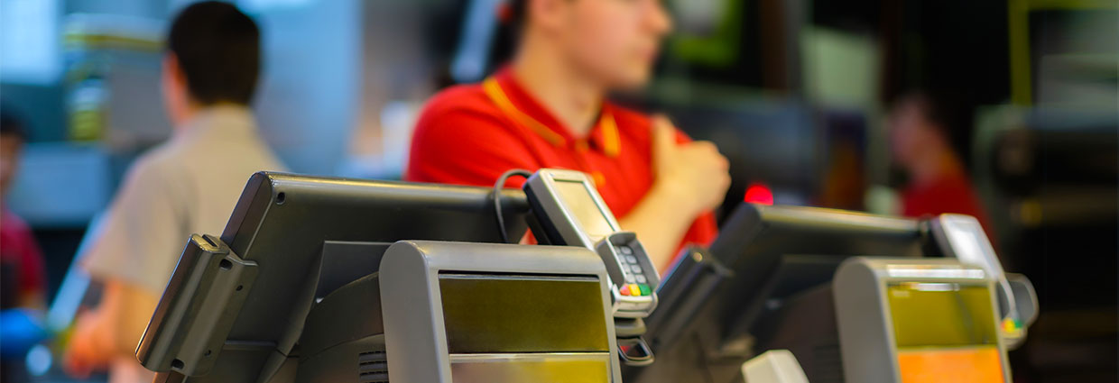 Cash and order desk with order screen and card payment terminal with cashiers on back in fast food restaurant